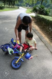 3181953-father-helping-son-getting-up-from-falling-off-bicycle-stock-photo